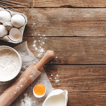 Baking ingredients, kitchen utensils on old wooden background. cooking dough, preparing egg yolk, flour, rolling pin, milk, parchment paper, whisk, salt, sodium. concept flat lay photo with copy space
