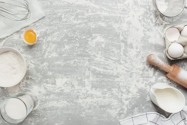 ベーキング材料、台所用品、灰色のコンクリートの背景に平らに置き、スペースをコピーします。クリスマスやお正月のクッキー、パン、ケーキの調理。卵、小麦粉、牛乳、油、バター、砂糖から生地を準備します