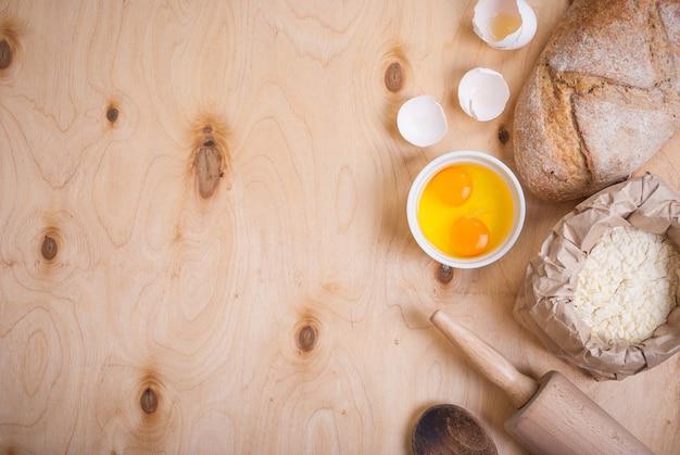Ингредиенты для выпечки на деревенском фоне с хлебом, яичной скорлупой, хлебом, мукой, скалкой