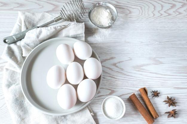 ベーキング材料-ナプキンとプレートの白い卵、白い木製のテーブルの上の小麦粉、イースターの組成物、モックアップ。