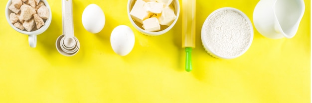 Baking ingredients on yellow background