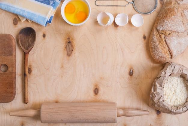 Выпечка светлый теплый фон с разделочной доской, яичной скорлупой, хлебом, мукой, скалкой. ингредиенты для запекания.
