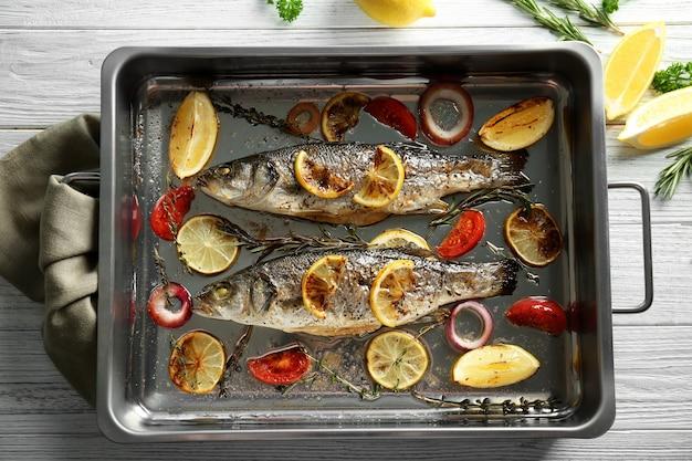 Форма для выпечки с рыбой морского окуня и гарниром на деревянном фоне