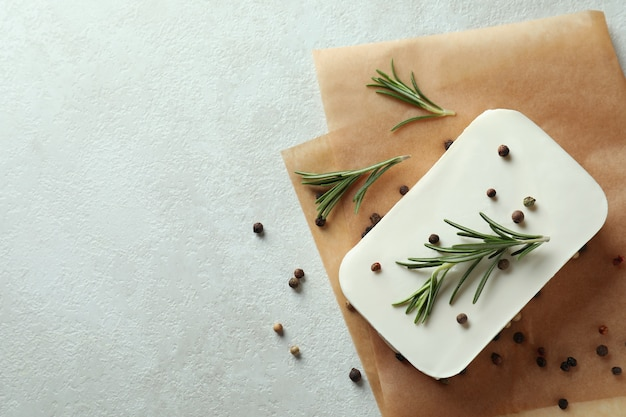 Baking paper with feta, pepper and rosemary on white textured