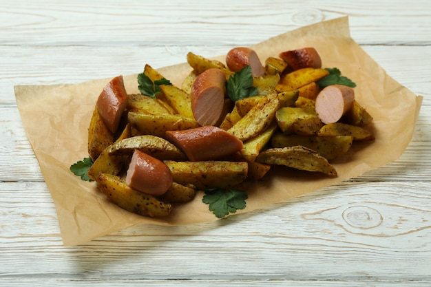 Baking paper with potato wedges and fried sausage on wooden