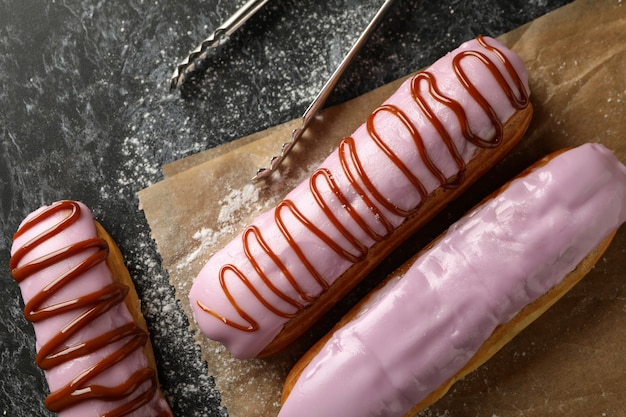 Baking paper with tasty eclairs on black smokey background