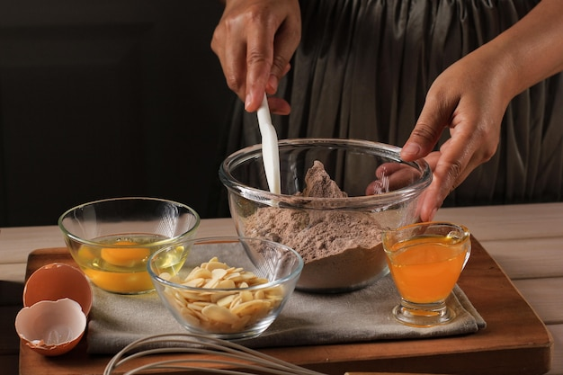 ベーキング準備材料:asian女性ハンドミックス小麦粉とチョコレートパウダー、周りに別の材料。チョコレートケーキの製造工程