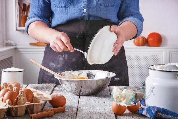 ベーキングの準備、生地をかき混ぜます。素朴な木製のテーブルに食材を調理する小麦粉、牛乳、バター、酵母、スパイス、卵のカートン。料理教室で女性シェフのパン屋