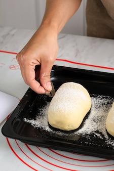 Процесс выпечки: приготовление хлеба, надрезание сырого круглого японского теста для хлеба с молочным подом. женская рука делает крест на верхней части теста с помощью бритвы