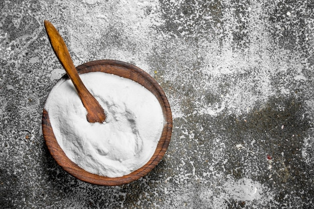 Baking soda in a bowl. on rustic background.