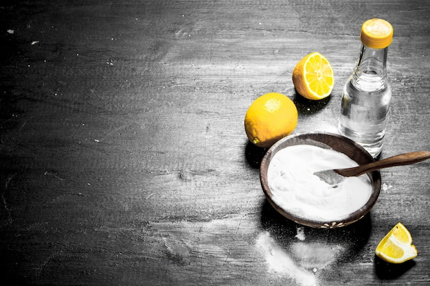 Baking soda in a bowl with vinegar and lemon slices.