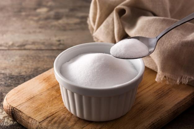 Пищевая сода в белом шаре на деревянном столе