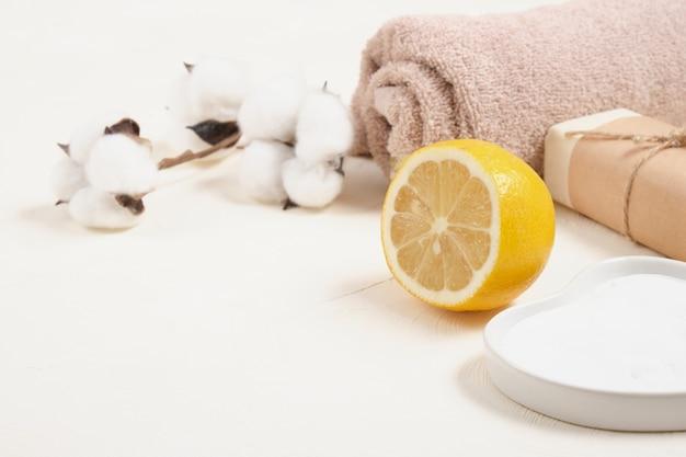 Пищевая сода, мыло, лимон, полотенце и цветок хлопка на светлом фоне copy space естественная концепция ухода за телом