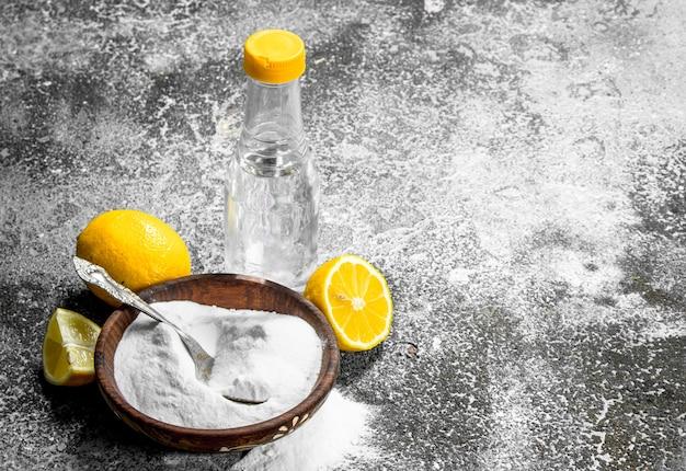 Пищевая сода с уксусом и лимоном. на деревенском фоне.