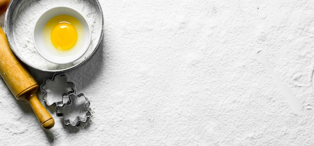 ベーキング面。卵、めん棒、生地の形をした小麦粉。小麦粉の白い表面に
