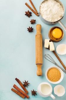 青い素朴なテーブルの上に小麦粉、卵、砂糖、バター、シナモン、アニススター、キッチンツールの材料で表面を焼く。セレクティブフォーカス。上面図。
