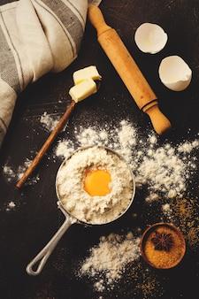 暗い古い素朴なテーブルの上に小麦粉、卵、砂糖、バター、シナモン、アニススター、キッチンツールの材料で表面を焼く。セレクティブフォーカス。トーン画像。上面図。