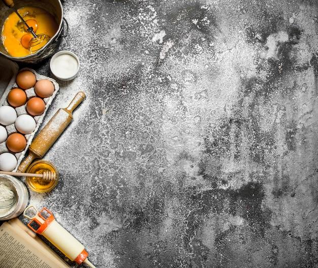 ベーキングテーブル。料理本からのさまざまな材料。素朴なテーブルの上。