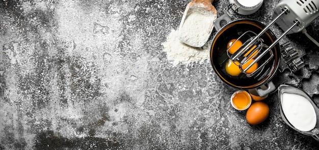 베이킹 테이블. 반죽을 만들기 위해 믹서로 계란을 섞는다. 소박한 테이블에.