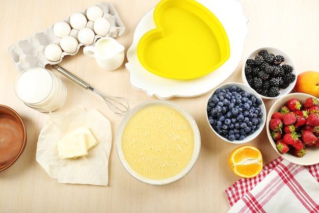 Выпечка вкусного пирога и ингредиенты для него на столе на кухне