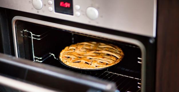 Выпечка традиционного яблочного пирога в духовке на кухне