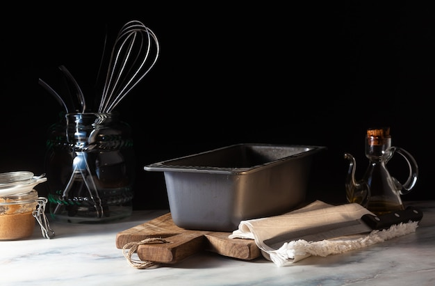A baking tray for baking bread on the kitchen table, dark background