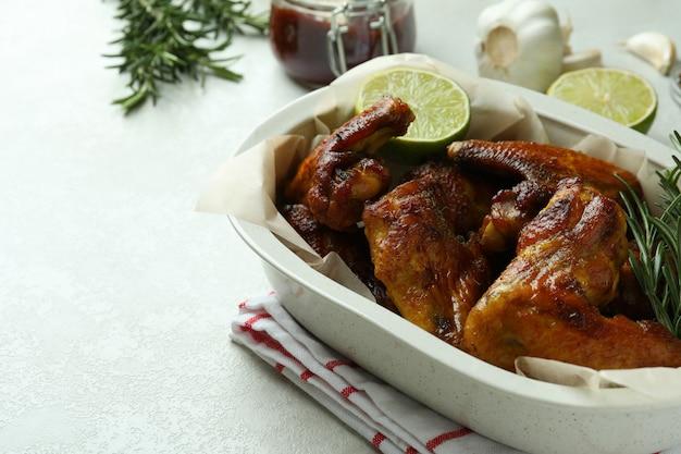 흰색 질감 된 테이블에 구운 닭 날개와 베이킹 트레이