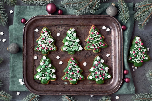 Baking tray with christmas tree cookies on dark gray textured wall with xmas decorations