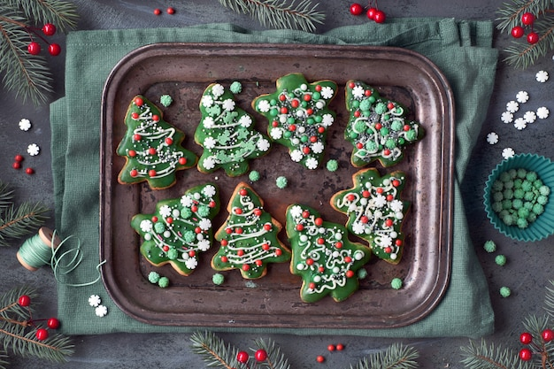Baking tray with christmas tree cookies with xmas decorations