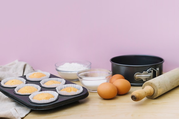 Baking tray with cupcakes and ingredients on wooden desk against pink background