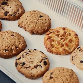 땅콩, 초콜릿 칩, 건포도와 함께 만든 채식 쿠키와 베이킹 트레이. 건강한 채식 음식을 먹습니다.