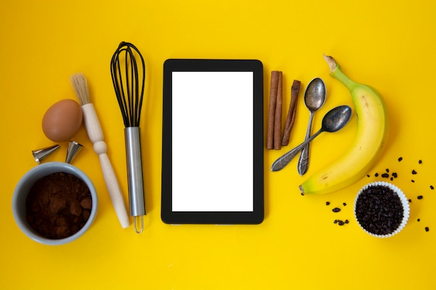 Baking utensiles and ingredients with tablet, on yellow background.