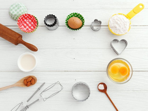 Baking utensils and ingredients frame on wooden table background with copy space in the middle