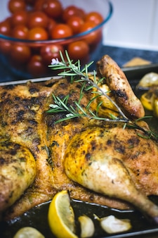 Baking whole chicken with lemon and cherry tomatoes