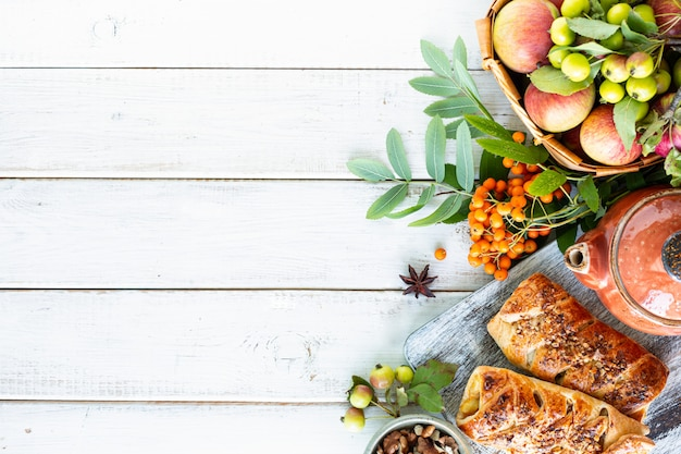 Выпечка с яблоком, свежеиспеченным яблоком и булочками с корицей из слоеного теста на белом деревянном столе. вид сверху, деревенский стиль, копия пространства.
