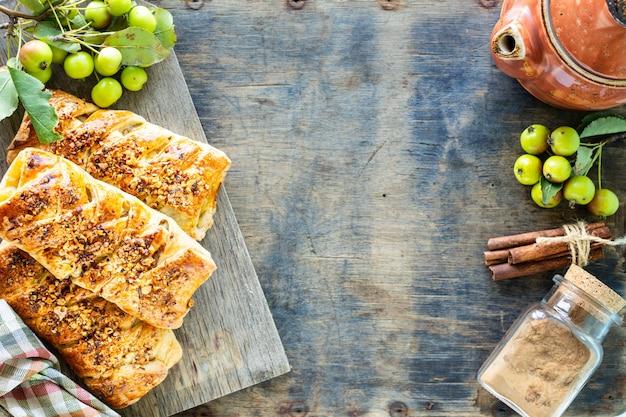 白い木製のテーブルの上で、リンゴ、焼きたてのリンゴ、パイ生地から作られたシナモンロールで焼く。上面図、素朴なスタイル、コピースペース。