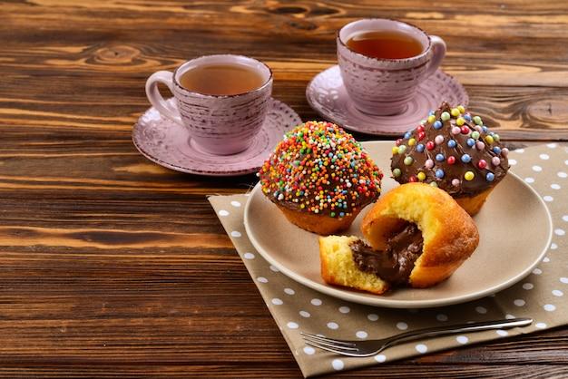 テーブルの上のお茶とチョコレートで焼く。テーブルの上の色とりどりのパウダーとカップケーキとチョコレートのお茶2杯。