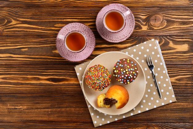 テーブルの上のお茶とチョコレートで焼く。テーブルの上の色とりどりの粉とチョコレートのカップケーキとチョコレートの2つのカップ。