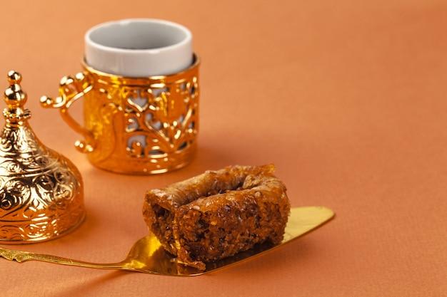 Пахлава десерт на золотой лопатке и кофейной чашке на бежевом фоне