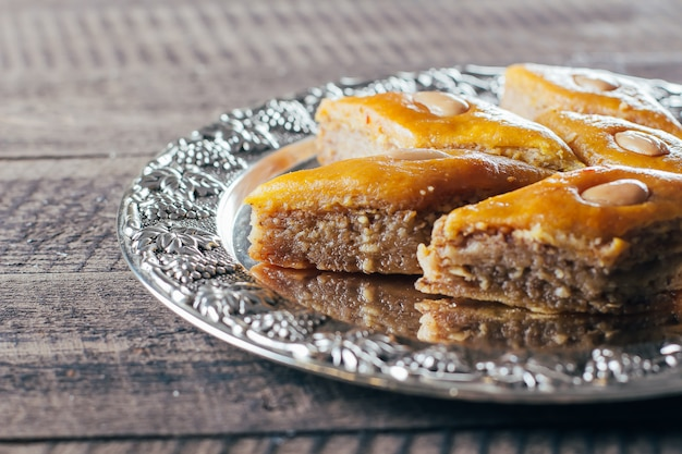Baklava. ramadan dessert.arabic dessert with nuts and honey, cup of tea on a wooden background.