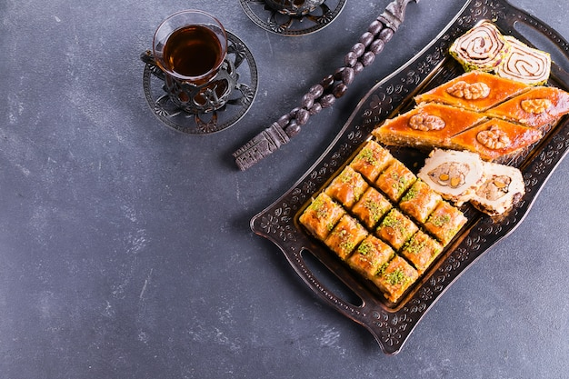 Baklava. ramadan dessert. assortment of arabic dessert with nuts and honey, cups of tea on a concrete table. top view, copy space
