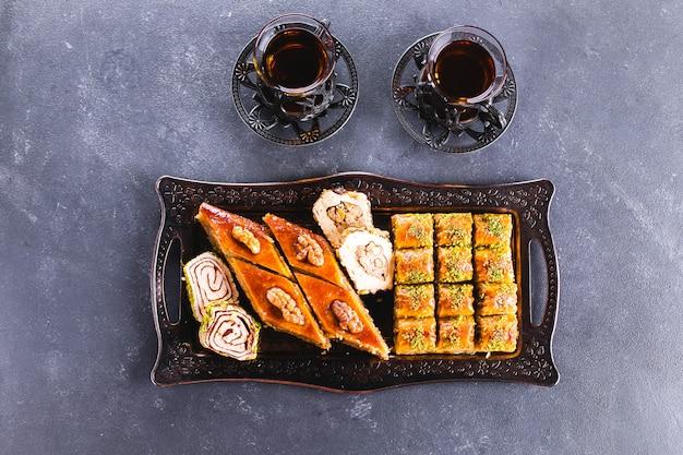 バクラバ。ラマダンデザート。ナッツと蜂蜜、具体的なテーブルにお茶のカップとアラビア語のデザートの品揃え。トップビュー、コピースペース