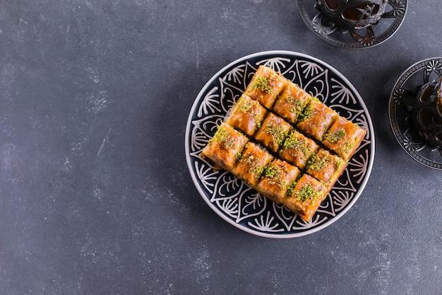 バクラバ。ラマダンデザート。ナッツと蜂蜜、コンクリートのテーブルでお茶を一杯と伝統的なアラビア語のデザート。トップビュー、コピースペース