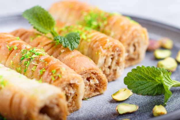 Baklava, traditional arabic sweets in gray ceramic plate on a gray concrete. close up.