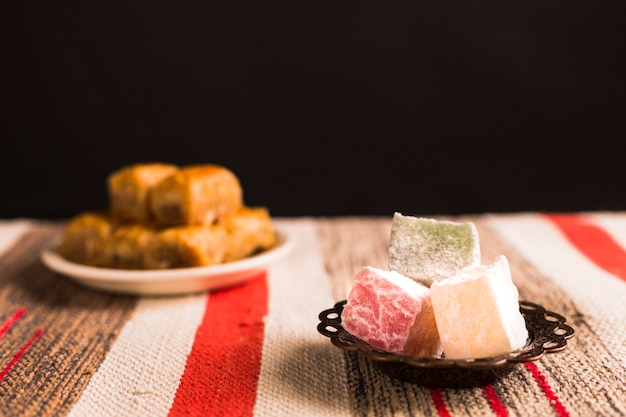 Baklava and turkish delights on saucers against mat