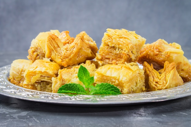 Baklava turkish traditional delight on a dark wood background. toning.