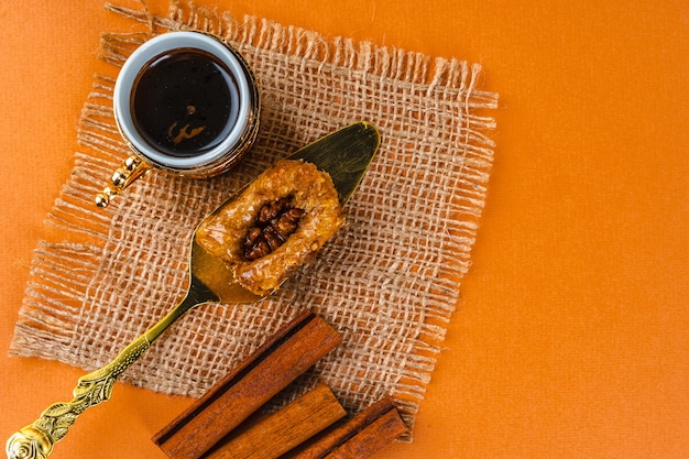 Пахлава с чашкой кофе и палочками корицы на оранжевом фоне