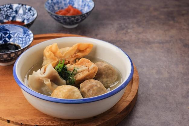 Баксо арема, фрикадельки, специальные блюда из маланга, восточная ява, индонезия. закройте вверх, на деревянной доске и деревенском столе. подается с соевым соусом, соусом и пастой из перца чили