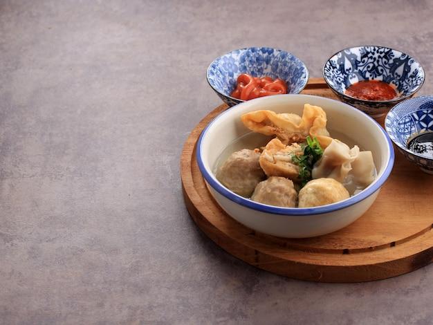 Баксо маланг, суп с фрикадельками с различными гарнирами, такими как жареный тофу шиумай или баксо горенг. подается на стол с самбалом, соевым и томатным соусами. выбранный фокус