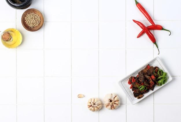 Balado paru、牛の肺から作られた伝統的なインドネシア料理。唐辛子、にんにく、エシャロット、ライムの葉をたっぷり使って調理。スパイシーな味わいで美味しいです。コピースペース